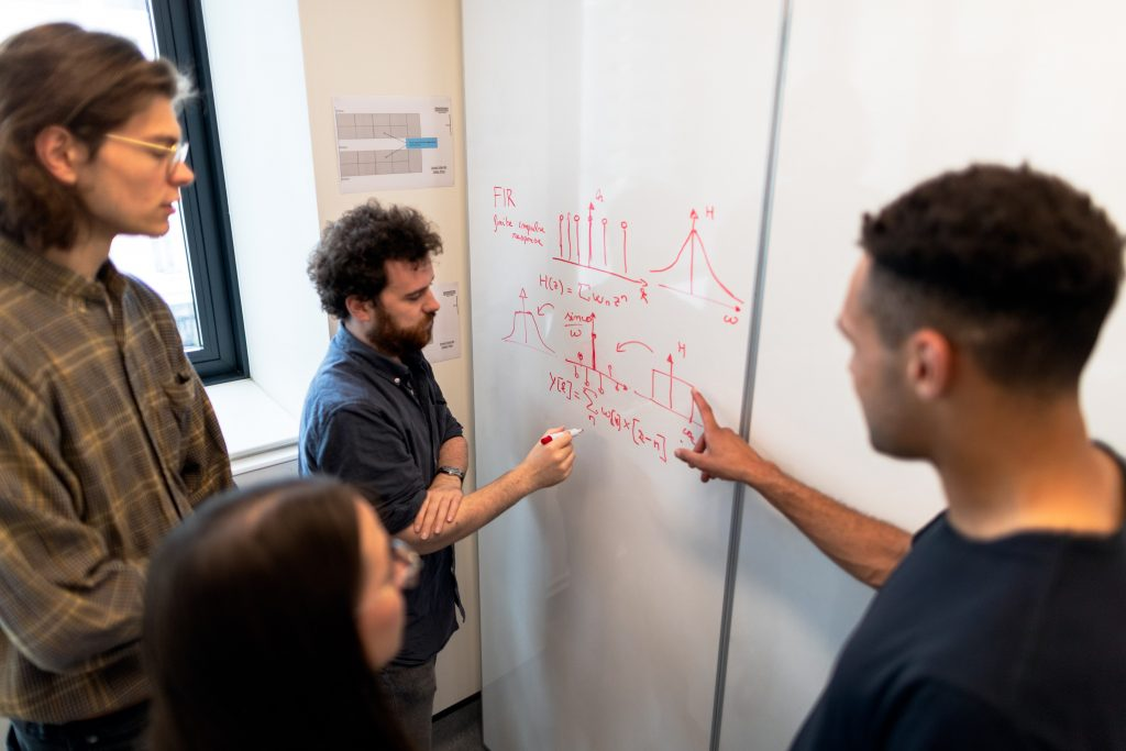 A group of scientists discuss equations at a whiteboard